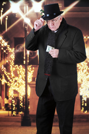 A miserly old man holding onto his top hat while clutching a wad of 100 dollar bills as he walks outside past a Christmas-decorated mall at night. Stock Photo