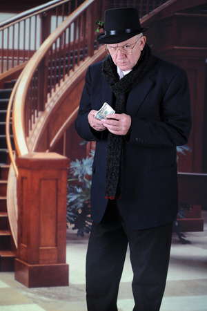 A senior man in black top hat and scarf, scowling at the viewer as he holds a fistful of 100 dollar bills as he walks past an elegant windiwng staircase. photo