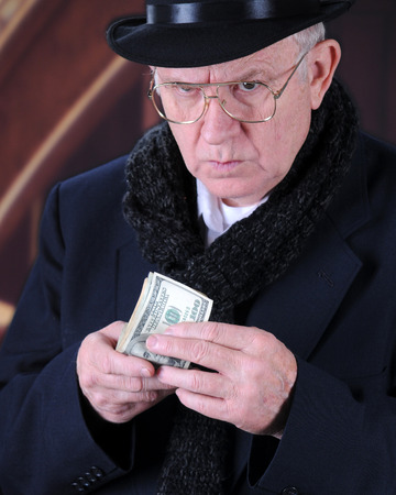 Close-up image of the miserly Mr. Scrooge looking up suspiciously while holding a fistful of 100 dollar bills. Stock Photo