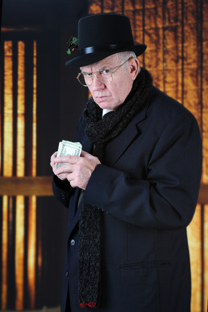 An old Mr. Scrooge in his top hat and scarf scowling at the viewer while holding a fistful of hundred-dollar bills close to his chest. Stock Photo