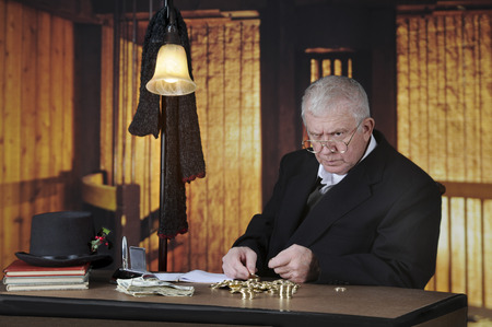miserly: A grumpy old miser sitting at his desk counting gold coins by a stack of big bills.