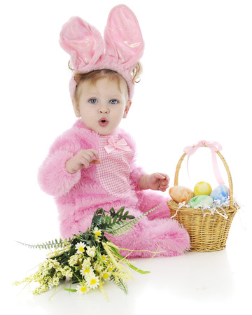 An adorable baby girl attempting to whistle in her fluffy pink Easter bunny outfit.  She sits beside a basket of colored eggs and a small bouquet of yellow flowers.  On a white background. photo