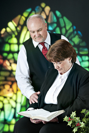 A mature adult couple reading scripture together before a colorful stained glass window. photo