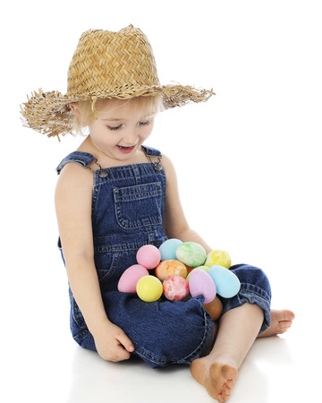 admiring: An adorable preschool farm girl looking delightedly at her lapfull of colorful Easter eggs.  On a white background.