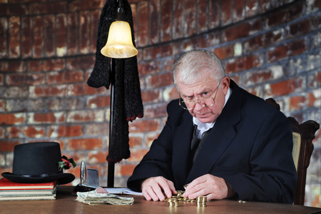 A grumpy old man scowling at the viewer as he counts his gold coins by a stack of large bills.