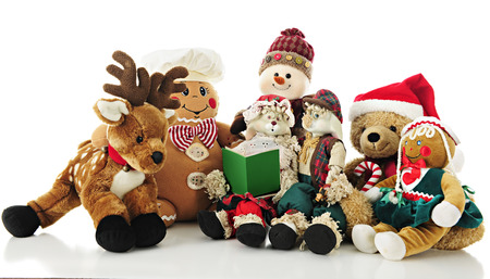 A collection of stuffed Christmas critters surrounding Ma Bunny who holds a Christmas carol book (or storybook) for the others to enjoy.  On a white background.