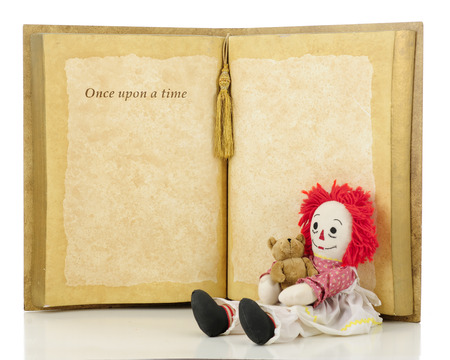 rick rack: A cheerful rag doll holding her baby sitting at the base of a huge opened book with the words Once upon a time.  Isolated on white.