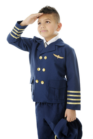 A handsome elementary airline pilot saluting with his hat to his side and right hand at his forehead.  On a white background. Imagens