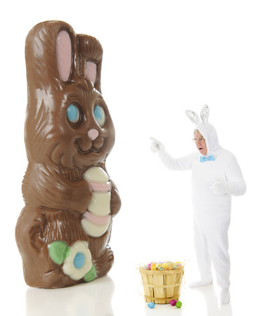 A senior man in a white rabbit outfit shociked while pointing to a giant chocolate bunny.  On a white background. photo