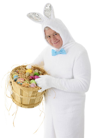 A senior adult man in a white bunny suit happily holding a bushel basket full of colorful eggs.  On a white background. photo