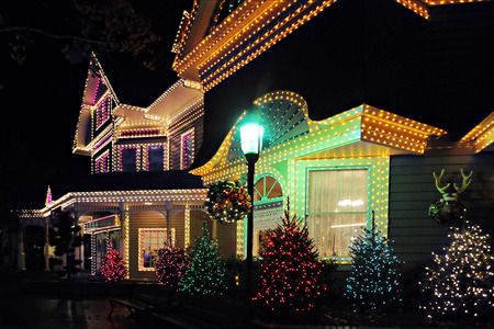 Nioght time image of a large, beautiful home all decked out in lights in celebration of Christmas. 新聞圖片