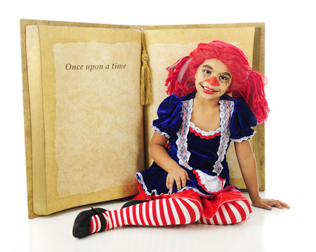 rick rack: A young elementary rag doll happily sitting before a huge opened book to a page with the words Once upon a time.  The rest of the page is left blank for your text.  On a white background.