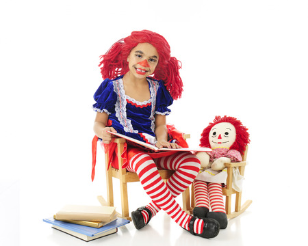 rag doll: An adorable elementary rag doll reading to her dolly with a small stack of books nearby.   Both rag dolls are sitting in their rocking chairs.  On a white background.