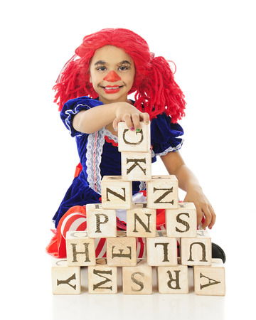 An adorable elementary rag doll happly making a pyramid with rustic alphabet blocks.  On a white background. photo