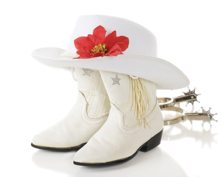 A pair of white cowgirl boots topped by a white hat with a red poinsettia with spurs laying nearby.  On a white background.