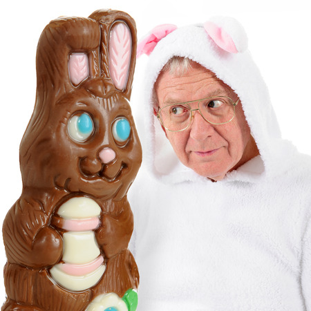 eyeing: A giant chocolate bunny and a senior-man bunny eyeing each other as if vying for top spot on the Easter bunny scene.  On a white background.