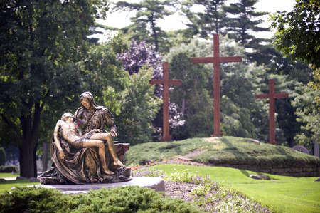 crucified: A bronze statue of Mary holding the crucified body of Jesus in a beautifully manicured cemetery.  Three wooden crosses are behind her.  Focus on statue.
