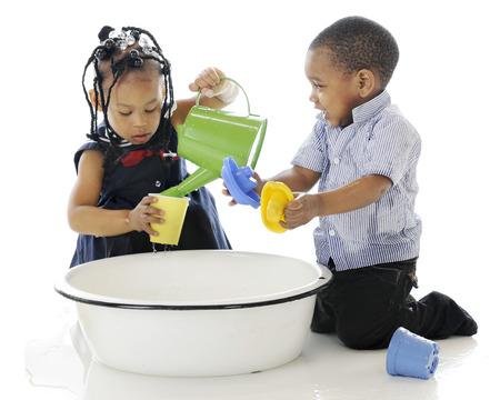 hermanos jugando: Un hermano y una hermana que se divierten jugando en una tina llena de juguetes para el agua y el agua. Sobre un fondo blanco.
