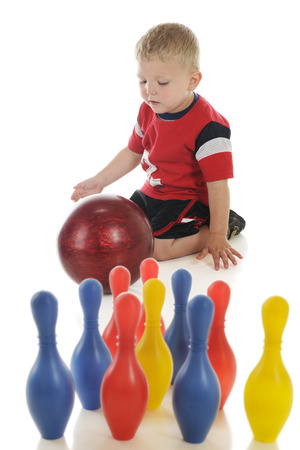A young preschooler attempting to roll a standard (heavy) bowling ball at his toy, plastic bowling pins.  Focus on boy.  On a white background.