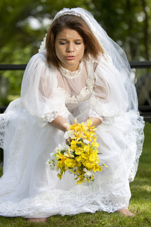 jilted: A pretty young summer bride distressed on her wedding day. Stock Photo