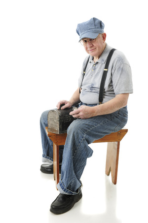 A senior adult train engineer sitting on an old wooden bench with his lunch box and pocket watch.  On a white background. photo