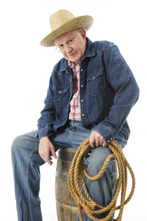 A senior adult cowboy still holding a rope while sitting on an old barrel looking at the viewer.  On a white background. photo