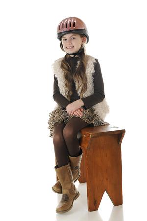riding helmet: Un jinete a caballo bastante elemental posando en su casco de montar y botas, sentados lado a la silla de montar en un viejo banco de madera. Foto de archivo