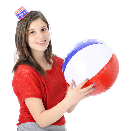 uncle sam hat: A beautiful young teen happily wearing a tiny Uncle Sam hat while holding an inflated red, white and blue ball.  On a white background. Stock Photo