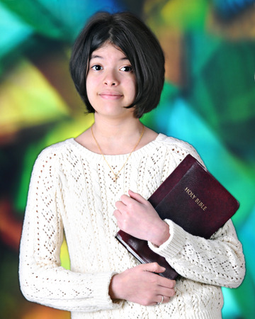 tween: A pretty young tween happily carrying her Bible befpre a large, stained glass window.