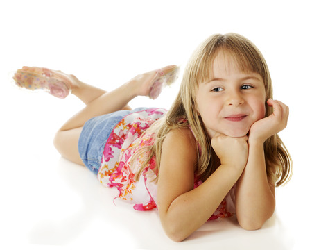 A pretty, young elementary girl happily relaxed on the floor with her head supported by her hands.  On a white background. photo