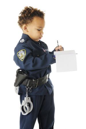 An adorable preschool traffic cop in uniform writing a ticken.  On a white background.