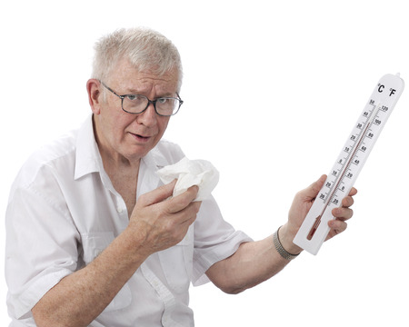 A senior man looking miserable as he holds a wiping tissue and thermometer reading in the high 90s F.  On a white background.