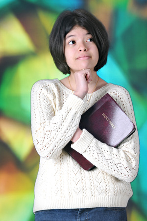 tween girl: A pretty tween girl thinking while holding her Bible before a large, stained glass window.