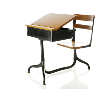 An antique school desk with an opened flip-top.  Isolated on white.
