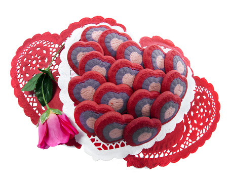 doilies: Multiple cookies arranged on heart-shaped doilies with a deep pink rose.  On a white background. Stock Photo