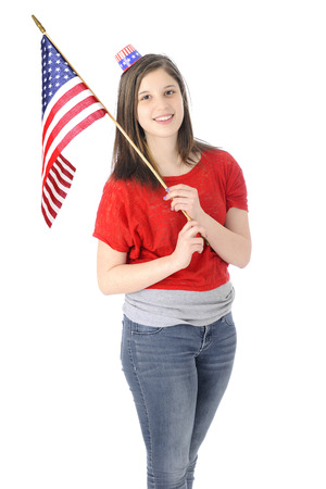 uncle sam hat: A pretty young teen wearing a tiny Uncle Sam hat while happily carrying an American flag.  On a white background.