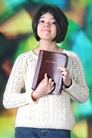 tween: A pretty tween girl proudly displaying her Bible for the viewer in front of a large, stained glass window.