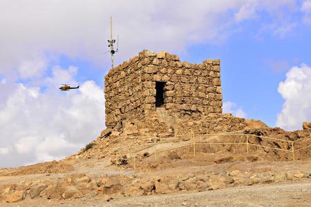 masada: A helicopter flying past an acient ruin atop Mount Masada, Israel.