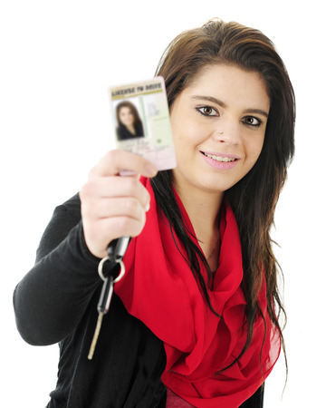 Close-up of a pretty teen girl happily holding up her new drivers license for the viewer to see, along with a car key.  Focus on teen.  On a white background.