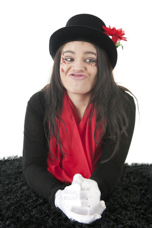A pretty teen girl, less than attractive, as she curls her lips for a kiss.  Her face is adorned with rhinestones and sparkly red hearts and shes wearing a black top hat, red scarf and white gloves.  On a whtie background. photo