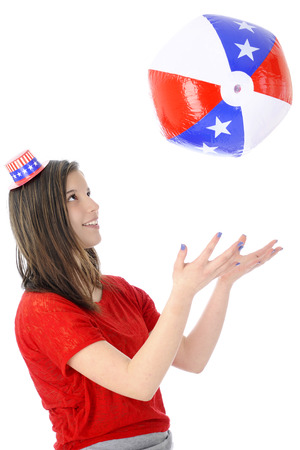 uncle sam hat: An attractive young teen wearing a tiny Uncle Sam hat.  Shes playing catch with an inflated star-studded red, white and blue ball.  On a white background.