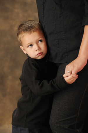 fear: Closel-up image of a shy preschooler clinging closely to his mother.  Shallow DOF with focus on boys face. Stock Photo
