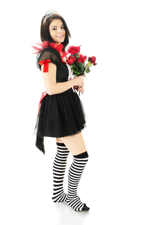 Side view of a  beautiful teen queen dressed in red, white and black happily standing with a bouquet of red roses.  On a white background. photo