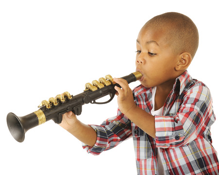 blowing of the wind: A handsome preschooler blowing his toy clarinet.  Isolated on white.