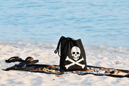 sandles: A black beach back with a smiling skull and crossbones with a towel and flip flops  on a sandy beach. Stock Photo