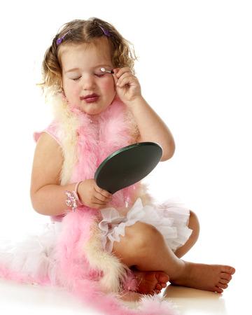 Un bambino in età prescolare adorabile in una sottoveste e boa rosa applicando il trucco di sua mamma su se stessa.