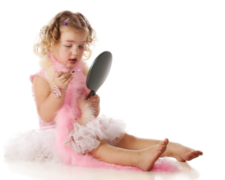 boas: A beautiful little girl in boas and a petticoat, applying her moms makeup on herself.  She appears to be wondering what to do with a littleeye-liner brush. Stock Photo