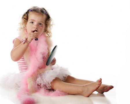 boas: Una ragazza adorabile prescolare applicando il trucco mentre vestito con boa e una sottoveste. Isolati su bianco.