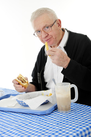 comida chatarra: Un hombre adulto mayor que goza de una comida de hamburguesa, papas fritas y un flotador rootbeer. Sobre un fondo blanco.