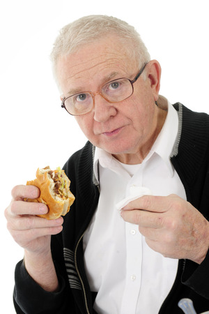 bifocals: Closeup of a senior man looking at the viewer with a half-eaten hamburger in one hand and a white napkin in the other.  On a white background.
